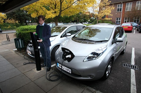 A man is connecting charging cable from a Nissan LEAF to a charging point at a car park