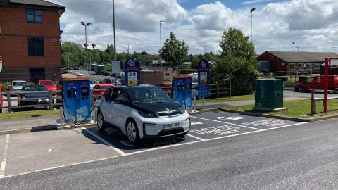 A BMW i3 charging in a designated charging space