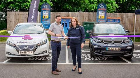 Representitives from Engenie and Octpus Energy cutting a purple ribbon to open their chargers