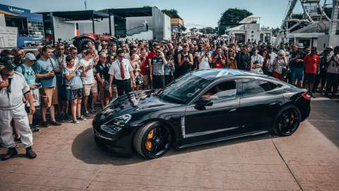 Side view of the Porsche Taycan amonst a croud