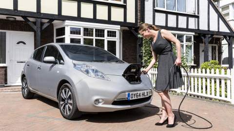 A woman charging up a Nissan Leaf