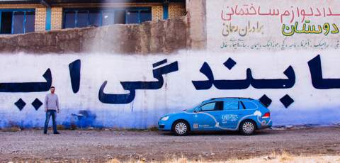Parked beside a wall with Persian writing on it