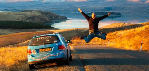 Wiebe jumping by his car infront of Lake Tekapo in New Zealand