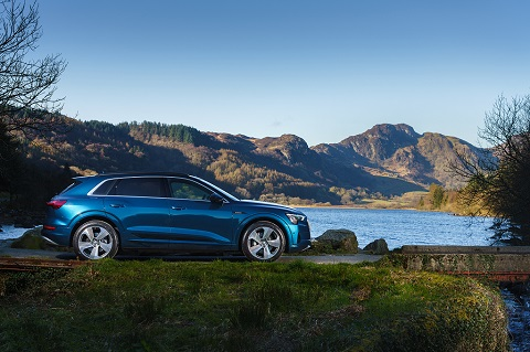 Side view on a blue Audi e-tron on a hilly background