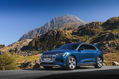 Exterior front passenger-side view of a blue Audi e-tron on a hilly background