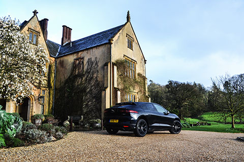 Jaguar I-PACE electric SUV next to a Manor