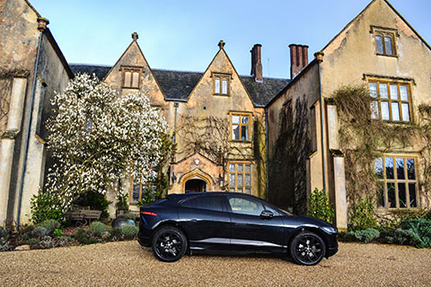 Jaguar I-PACE electric SUV exterior side view next to a Manor