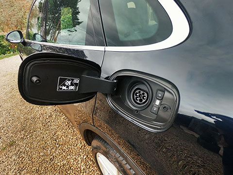 Porsche Cayenne E-Hybrid charging open flap exposing socket close view